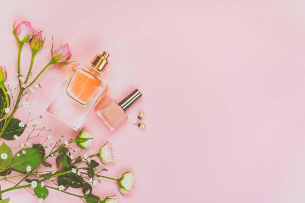 wohnung lag der weiblichen kosmetikprodukte und zubehör. eine flasche parfüm, nude nagellack, perlen ohrringe und rosen auf rosa hintergrund. kopieren sie raum. - ohrringe rose stock-fotos und bilder