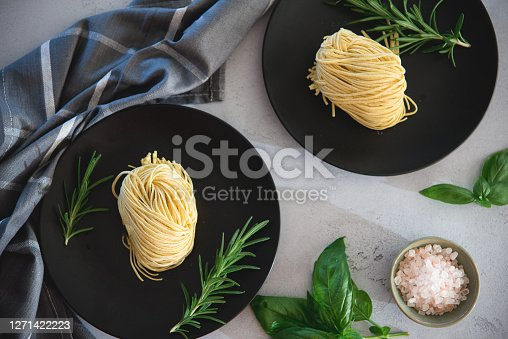 Flat lay of fresh homemade pasta on plate with rosemar