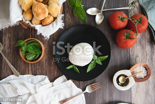 Flat lay of fresh mozarella cheese, tomatoes, basil, and fresh home made bread
