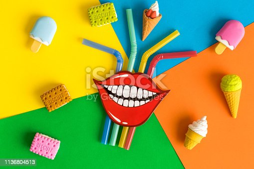Paper prop smile with drinking straws, ice cream and biscuits against colorful background minimal creative concept.