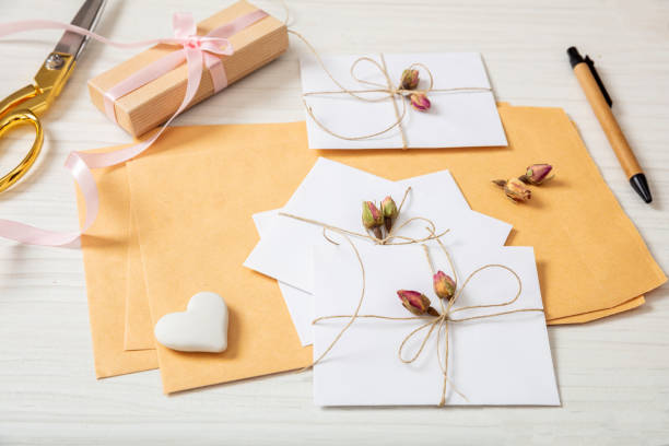 flat lay of gift box and invitations on a white wooden tabletop, background. - religious celebration stock photos and pictures