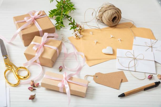 wohnung von geschenk-boxen und einladungen auf einer weißen hölzernen tischplatte legen - geschenk zur taufe stock-fotos und bilder