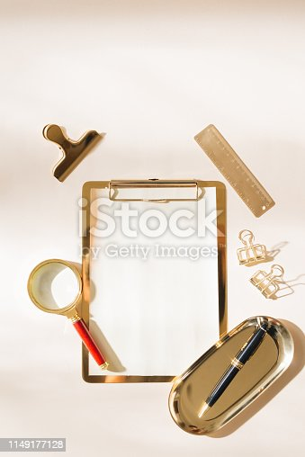 Flat lay of gold stationery on light background
