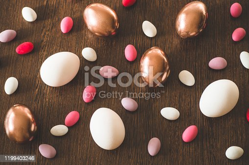 1135121547 istock photo Flat Lay of Golden and multi-color Easter Eggs Pattern on wooden background. Easter background or easter concept 1199403246