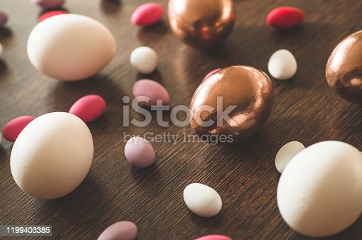 1135121547 istock photo Flat Lay of Golden and multi-color Easter Eggs Pattern on wooden background. Easter background or easter concept 1199403385