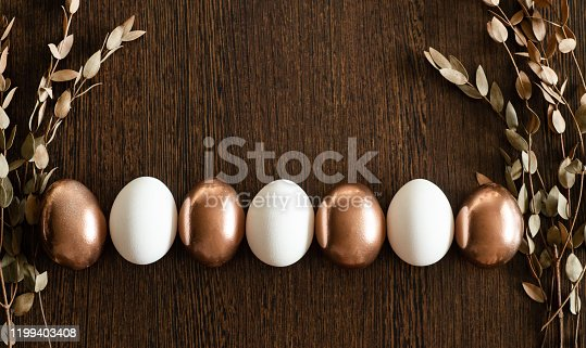 1135121547 istock photo Flat Lay of Golden and multi-color Easter Eggs Pattern on wooden background. Easter background or easter concept 1199403408