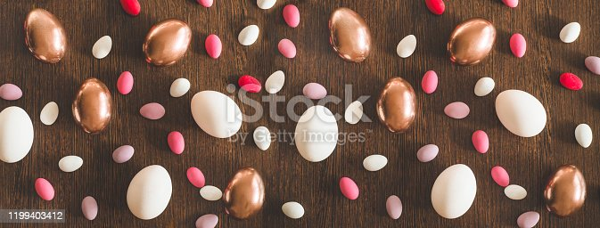1135121547 istock photo Flat Lay of Golden and multi-color Easter Eggs Pattern on wooden background. Easter background or easter concept 1199403412