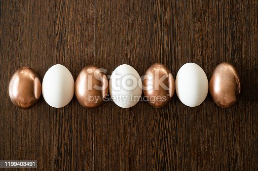 1135121547 istock photo Flat Lay of Golden and multi-color Easter Eggs Pattern on wooden background. Easter background or easter concept 1199403491
