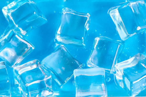 Plano de cubitos de hielo en líquido azul. - foto de stock
