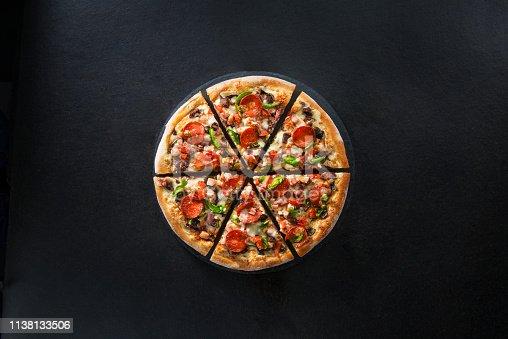 istock Flat lay of italian pizza on dark surface top view 1138133506