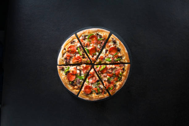 Flat lay of italian pizza on dark surface top view Italian pizza on dark background pizza stock pictures, royalty-free photos & images
