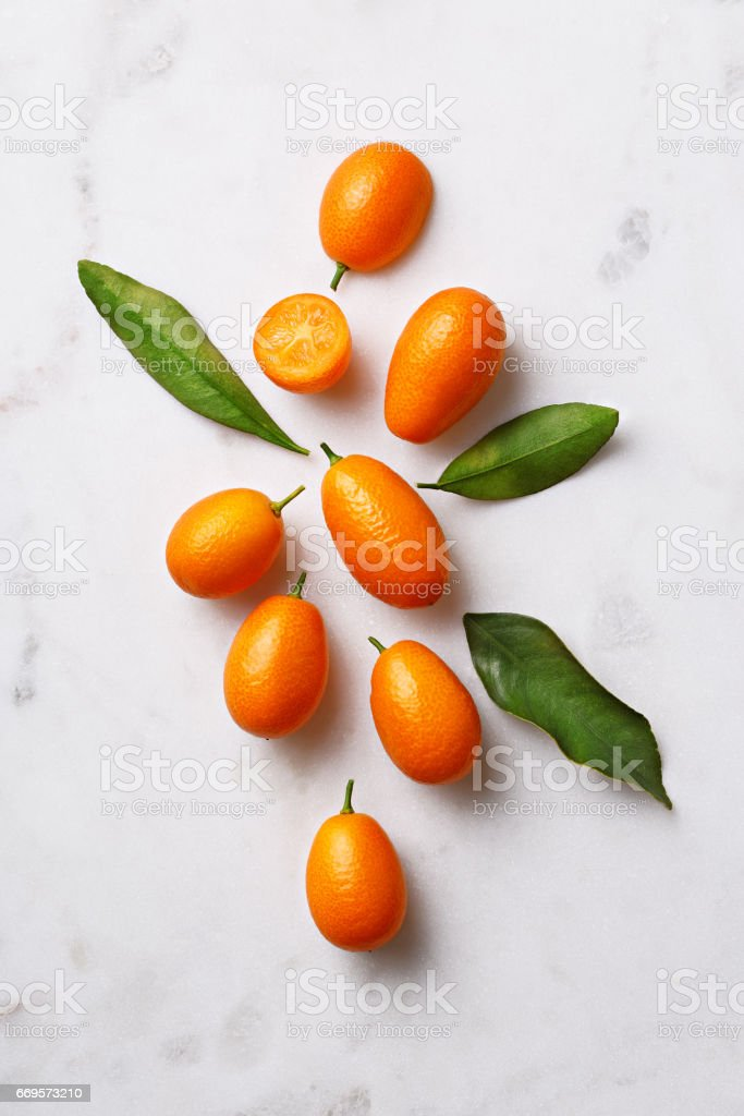 Flat lay of kumquats on a marble background. Top view stock photo