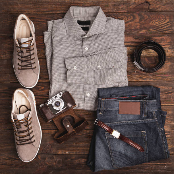 flat lay of modern men's clothing on a wooden background - menswear stock photos and pictures