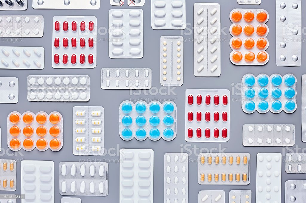 Flat lay of multi colored blister packs on gray background - foto de stock