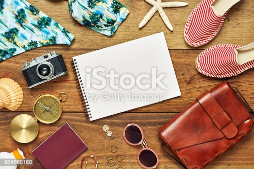 istock Flat lay of note pad surrounded with beach travel accessories 624566160
