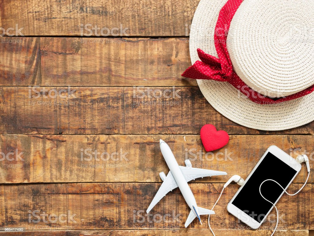 flat lay of plane model , red heart shape ,mobile ,earphone and woman hat as traveler's accessories items on wooden background with copy space inside colorful bead frame. travel and vacation for girl zbiór zdjęć royalty-free