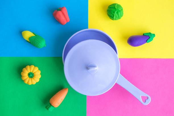 wohnung lag der kunststoffwanne mit verschiedenen kautschuk spielzeug gemüse auf farbigen hintergrund minimal kreativkonzept. - chefkoch auflauf stock-fotos und bilder
