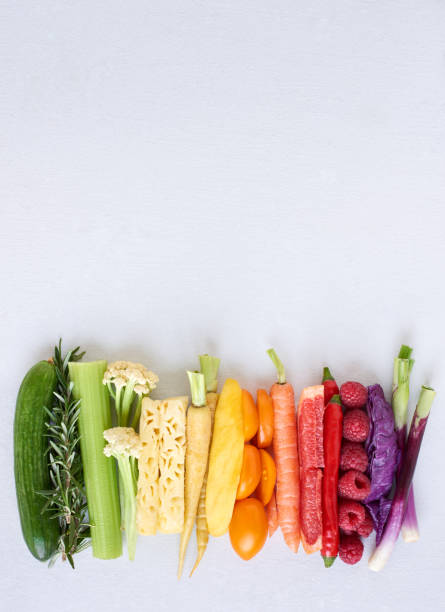 flat lay of rainbow spectrum gradient of healthy fruit and vegetables on white background - antiossidante foto e immagini stock