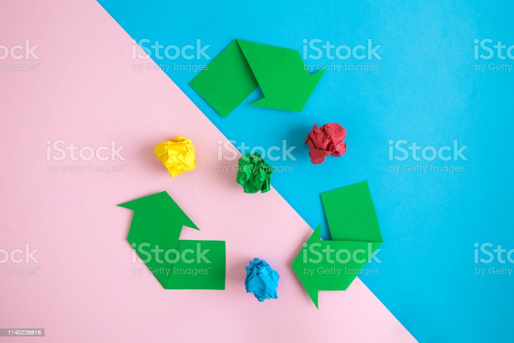 Recycle symbol with crumpled paper on colorful background minimal eco...