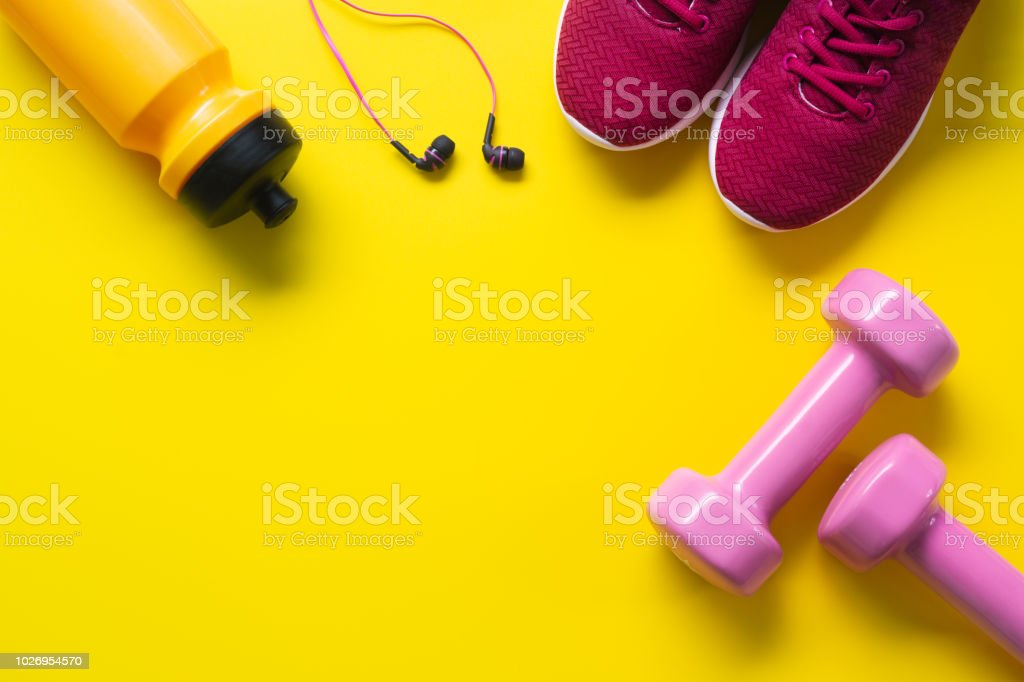 Flat lay of red sport shoes, pink dumbbells, earphones, bottle of water on yellow  background. Active Healthy lifestyle, working out, weight and dieting concept. royalty-free stock photo