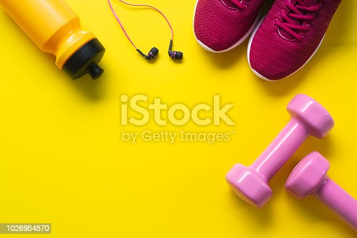 istock Flat lay of red sport shoes, pink dumbbells, earphones, bottle of water on yellow  background. Active Healthy lifestyle, working out, weight and dieting concept. 1026954570