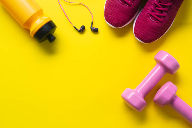 flat lay of red sport shoes, pink dumbbells, earphones, bottle of water on yellow  background. active healthy lifestyle, working out, weight and dieting concept. - тренажер стоковые фото и изображения