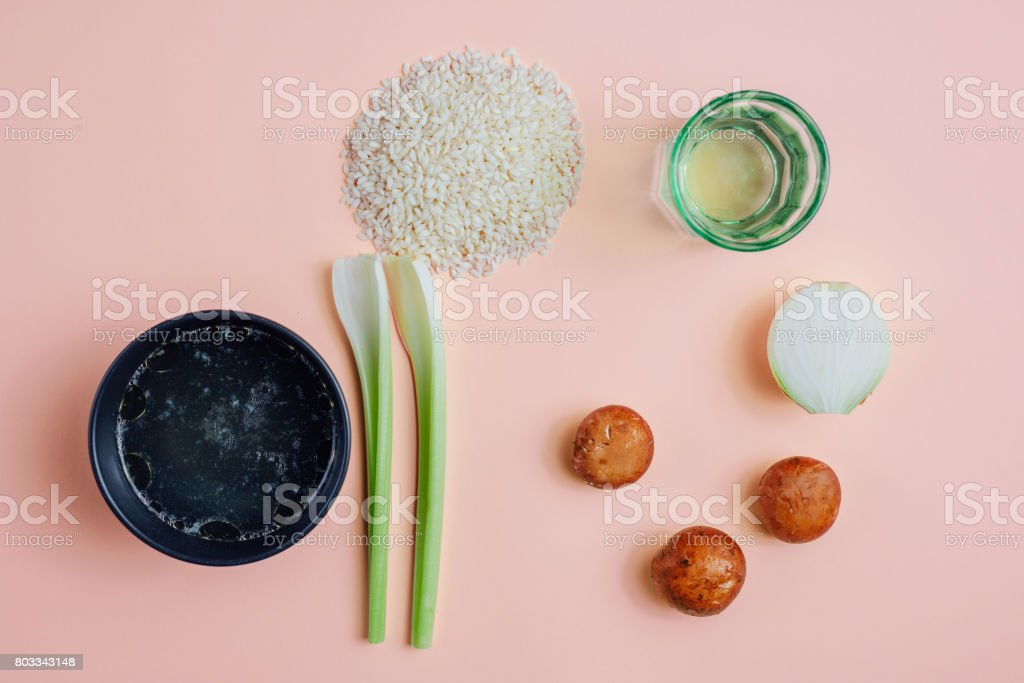 Flat lay of risotto ingredients against pastel pink background stock photo