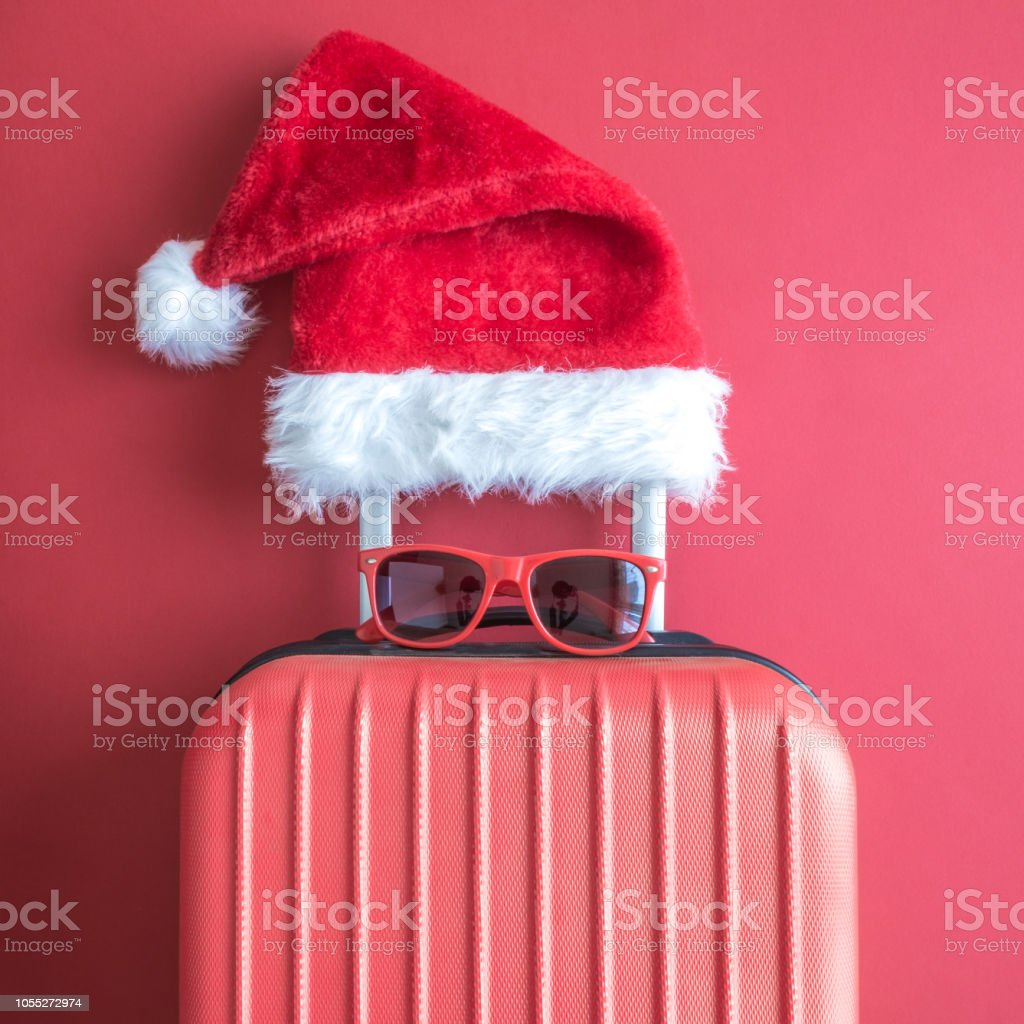 Flat lay of Santa Claus hat, sunglasses and luggage abstract isolated on red. royalty-free stock photo
