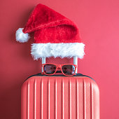 Suitcase with Santa hat and sunglasses on red background minimal creative concept.