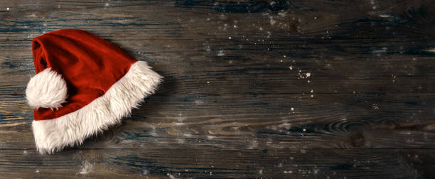 flat lay of santa's hat on wooden background - santa hat stock pictures, royalty-free photos & images