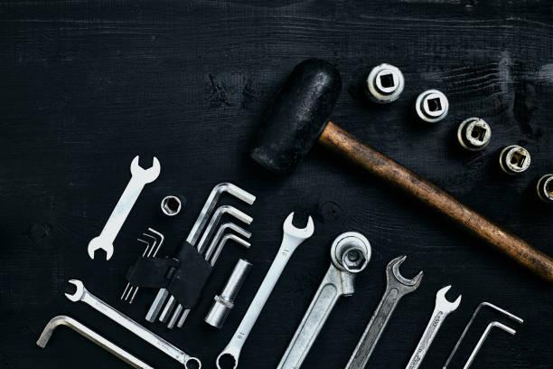 Apartamento leigos do conjunto de ferramentas para carro reparando como chaves em fundo preto de madeira. Vista superior - foto de acervo