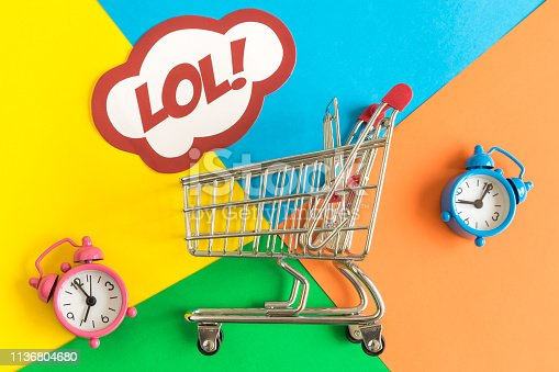 istock Flat lay of shopping cart and lol text in speech bubble with alarm clocks against colorful background minimal creative concept. 1136804680
