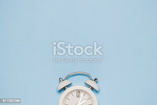 1139289535 istock photo Flat lay of small alarm clock on blue background 917262296