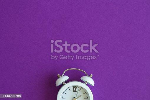 1139289535 istock photo Flat lay of small alarm clock on purple background 1140226788