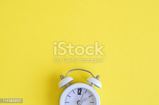 1139289535 istock photo Flat lay of small alarm clock on yellow background 1141610121
