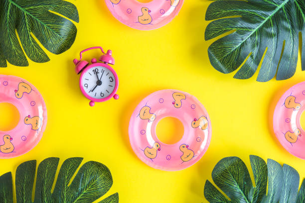 flat lay of small swimming pool floats with alarm clock and green leaves isolated on yellow. summertime concept. - climate clock imagens e fotografias de stock