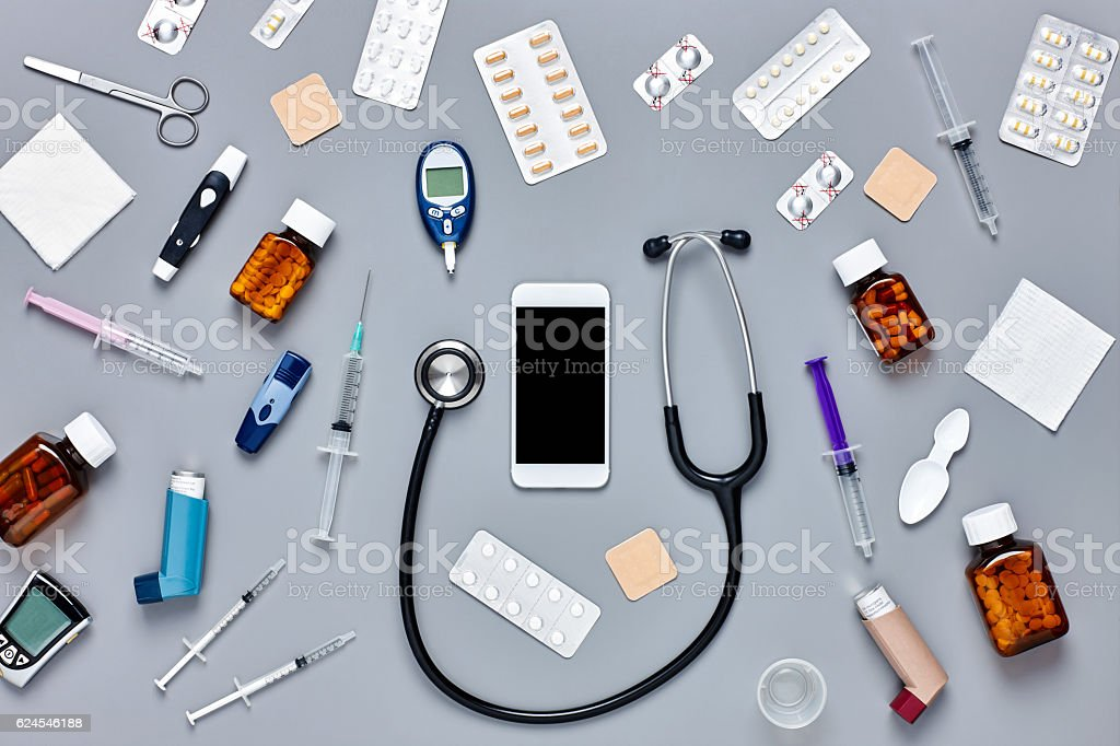 Flat lay of smart phone surrounded with medical equipment stock photo