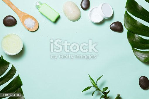 Flat lay of spa cosmetic with bamboo, salt for bath, cream and towel on pastel background, top view mock-up