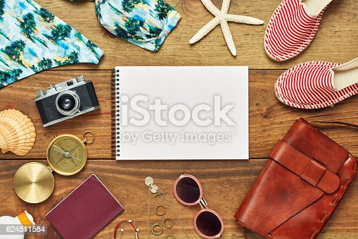 941183588 istock photo Flat lay of spiral notebook surrounded with beach travel accessories 624511584
