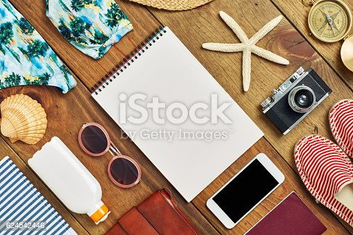 941183588 istock photo Flat lay of spiral notebook surrounded with beach travel accessories 624542446