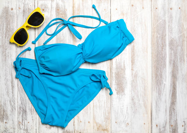 Flat lay of summer items with colorful bikini and accessories on white wooden background, Summer concept, Copy space Flat lay of summer items with colorful bikini and accessories on white wooden background, Summer concept, Copy space swimwear stock pictures, royalty-free photos & images