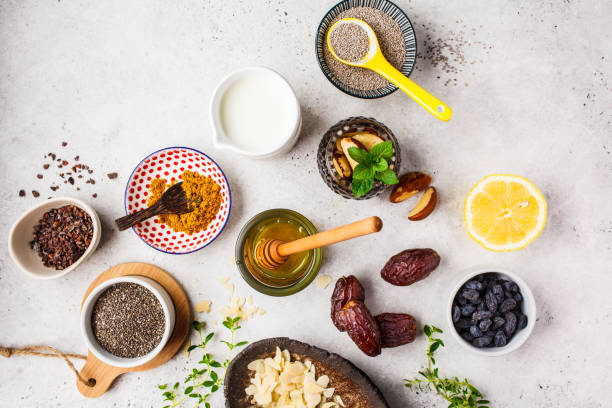 Flat lay of super foods on white background. Cooking healthy food concept. Flat lay of super foods - honey, dates, milk, turmeric, lemon, nuts and chia on a white background. Cooking healthy food concept. anti inflammatory stock pictures, royalty-free photos & images