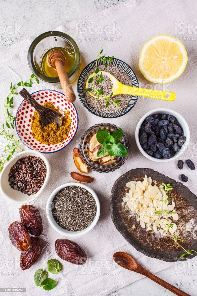 Flat lay of super foods - honey, dates, turmeric, lemon, nuts and...