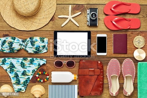 941183588 istock photo Flat lay of tablet computer surrounded with beach travel accesso 624541902