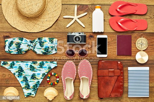 istock Flat lay of travel and beach accessories on wood 624529858