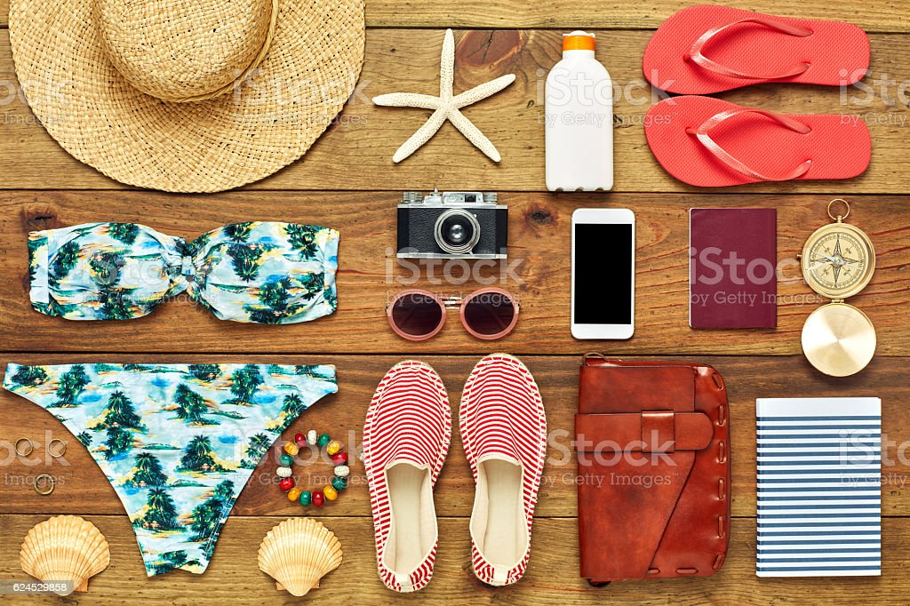 Flat lay of travel and beach accessories on wood stock photo
