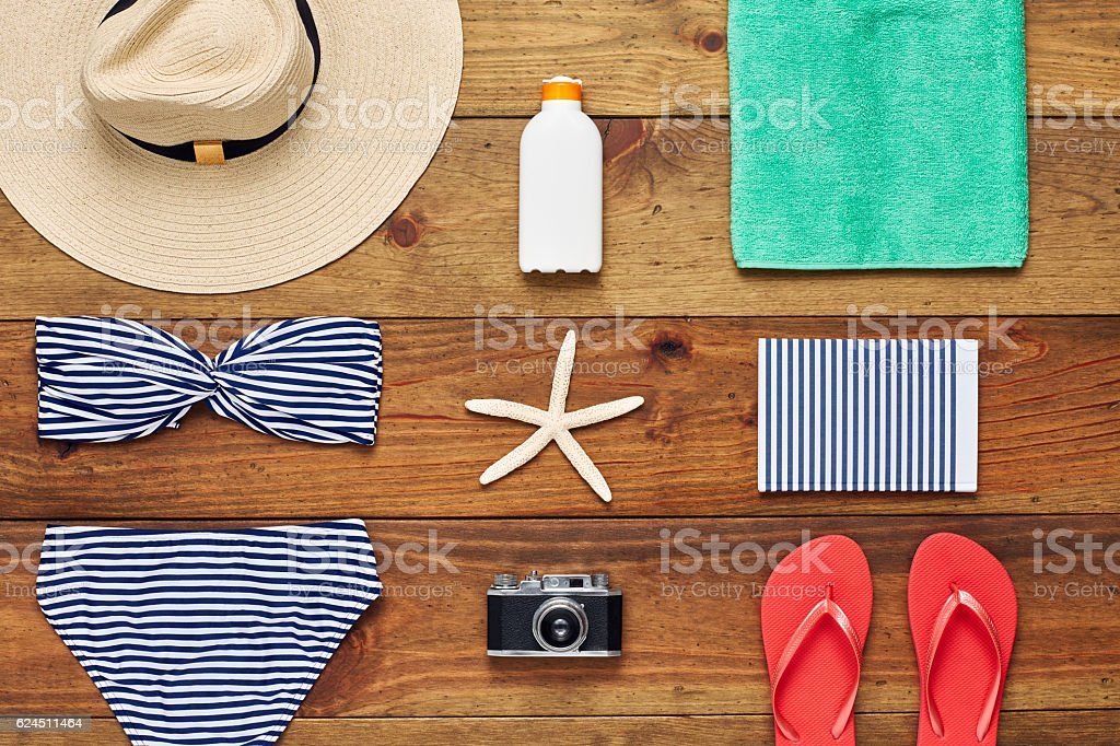 Flat lay of travel and beach accessories on wooden floor stock photo