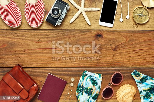 941183588 istock photo Flat lay of travel and beach accessories on wooden floor 624512048