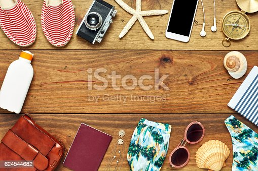 941183588 istock photo Flat lay of travel and beach accessories on wooden floor 624544682