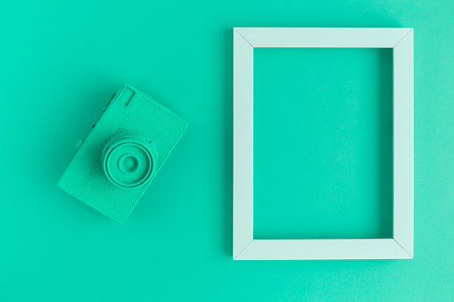 istock Flat lay of turquoise vintage camera and photo frame background 951691212